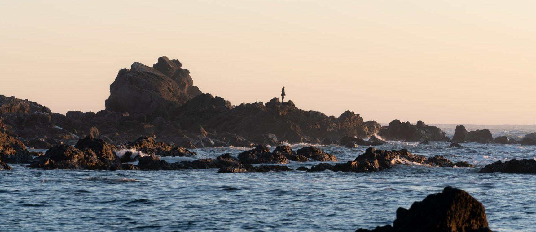 Person on rocky shoreline, Ucluelet BC